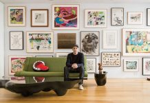 KAWS sitting in front of his extensive art collection : Photo by © Stefan-Ruiz