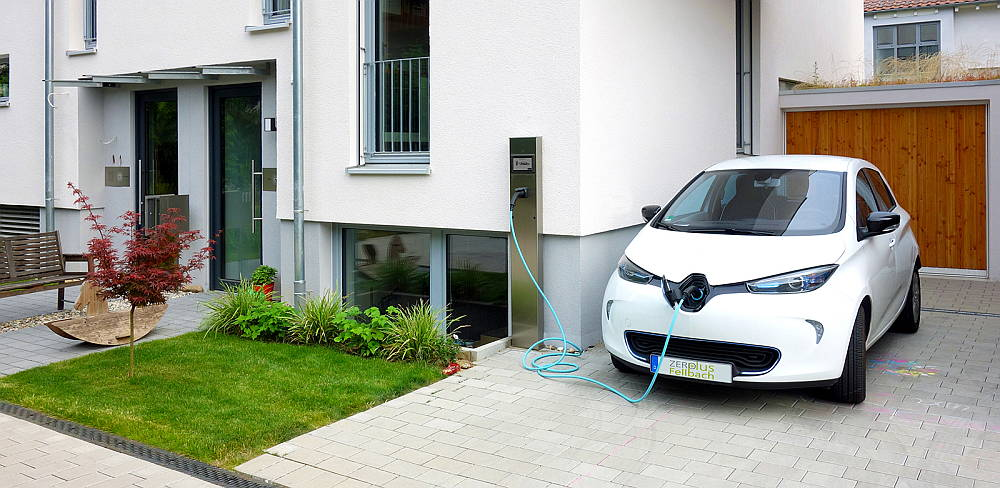 An electric vehicle is charged with photovoltaic power from the roof of the house using a charging station: Photo © Fraunhofer ISE