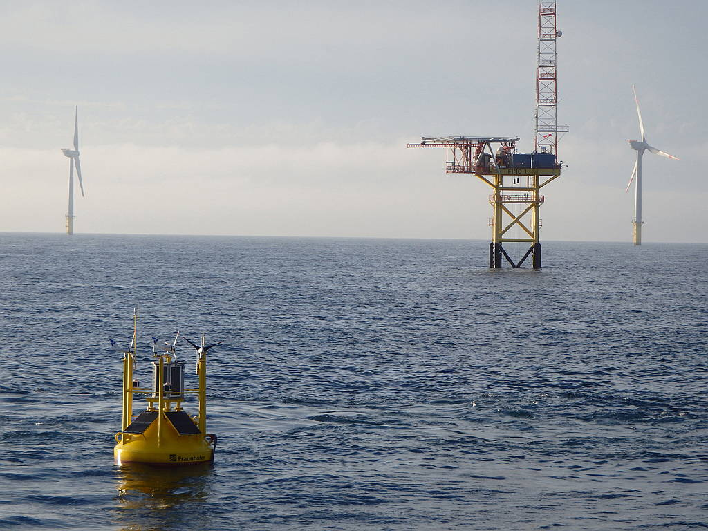 In the North Sea, wind measurement buoy with sophisticated, precise measurement technology situated in front of the FINO 1 wind met mast © Photo: Fraunhofer IWES