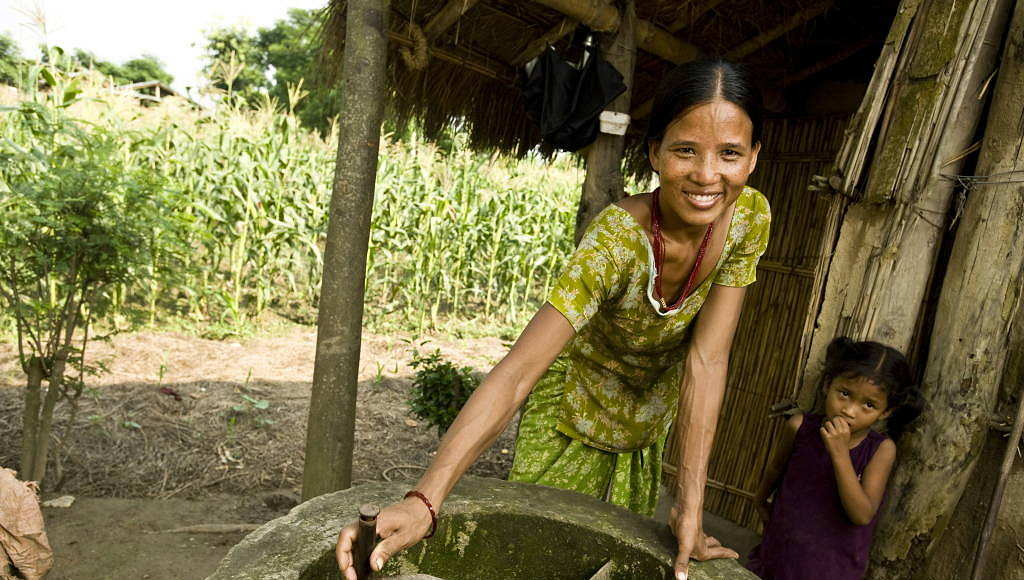 A woman turns the manure stirrer outside her home in a bio gas village on the outskirts of Chitwan National Park, Nepal : Photo © Simon de Trey-White / WWF-UK