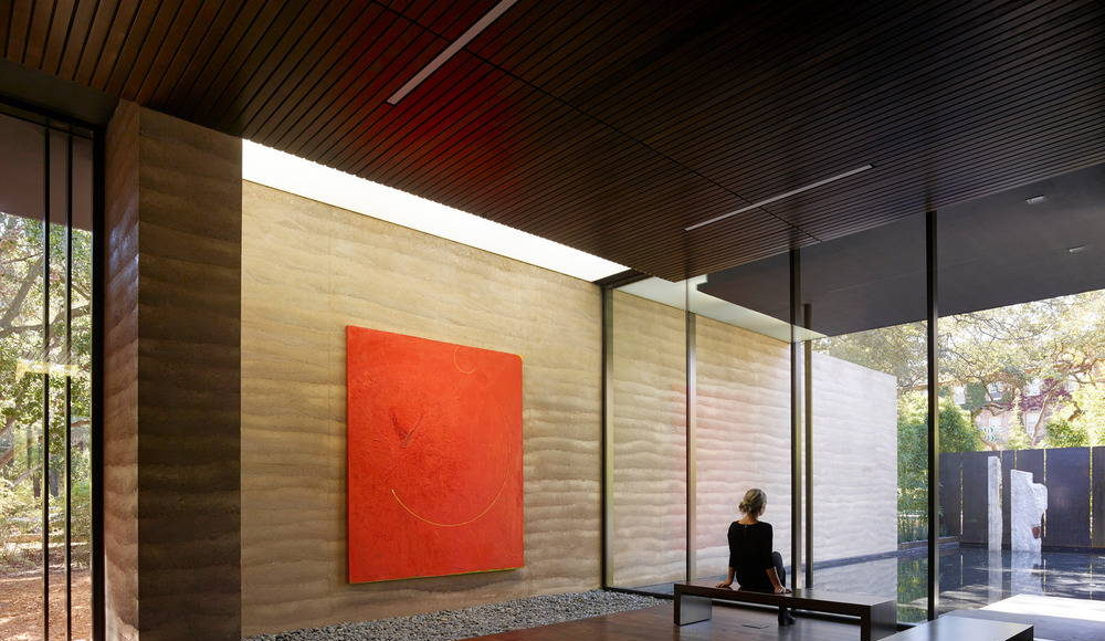 """Nathan Oliveira's """"Big Red"""" greets visitors upon entering the building. The rammed earth wall extends from the entry to the reflecting pool beyond, blurring the line between interior and exterior : Photo credit © Matthew Millman"""