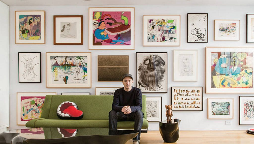 KAWS sitting in front of his extensive art collection : Photo by © Stefan Ruiz