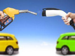 Automóvil eléctrico y auto concepto de gasolina. mano sosteniendo bomba de gasolina y conector para recarga de energía vía Shutterstock