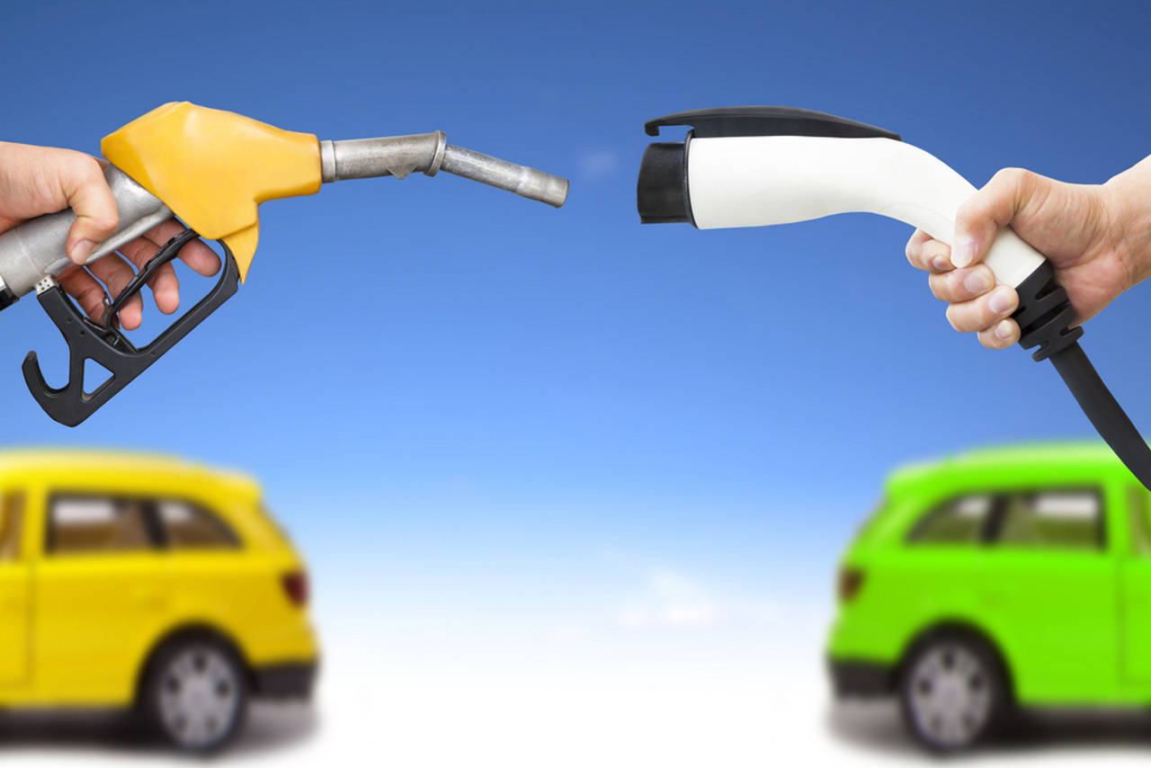 Electric car and gasoline car concept. hand holding gas pump and power connector for refuel via Shutterstock