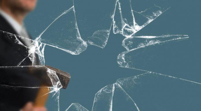 Business Man with Sledgehammer behind a broken Glass Pane vía Shutterstock