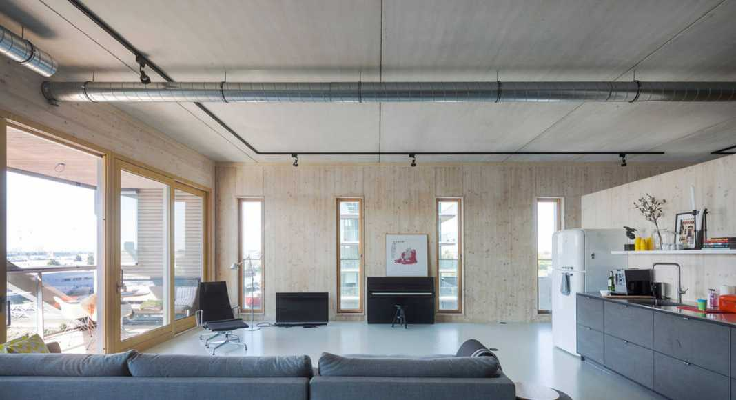 Apartment 9: an open floorplan appartment for a family with to teenage doughters. The structural wooden wall of the west facade is present in the complete space : Photo credit © Luuk Kramer