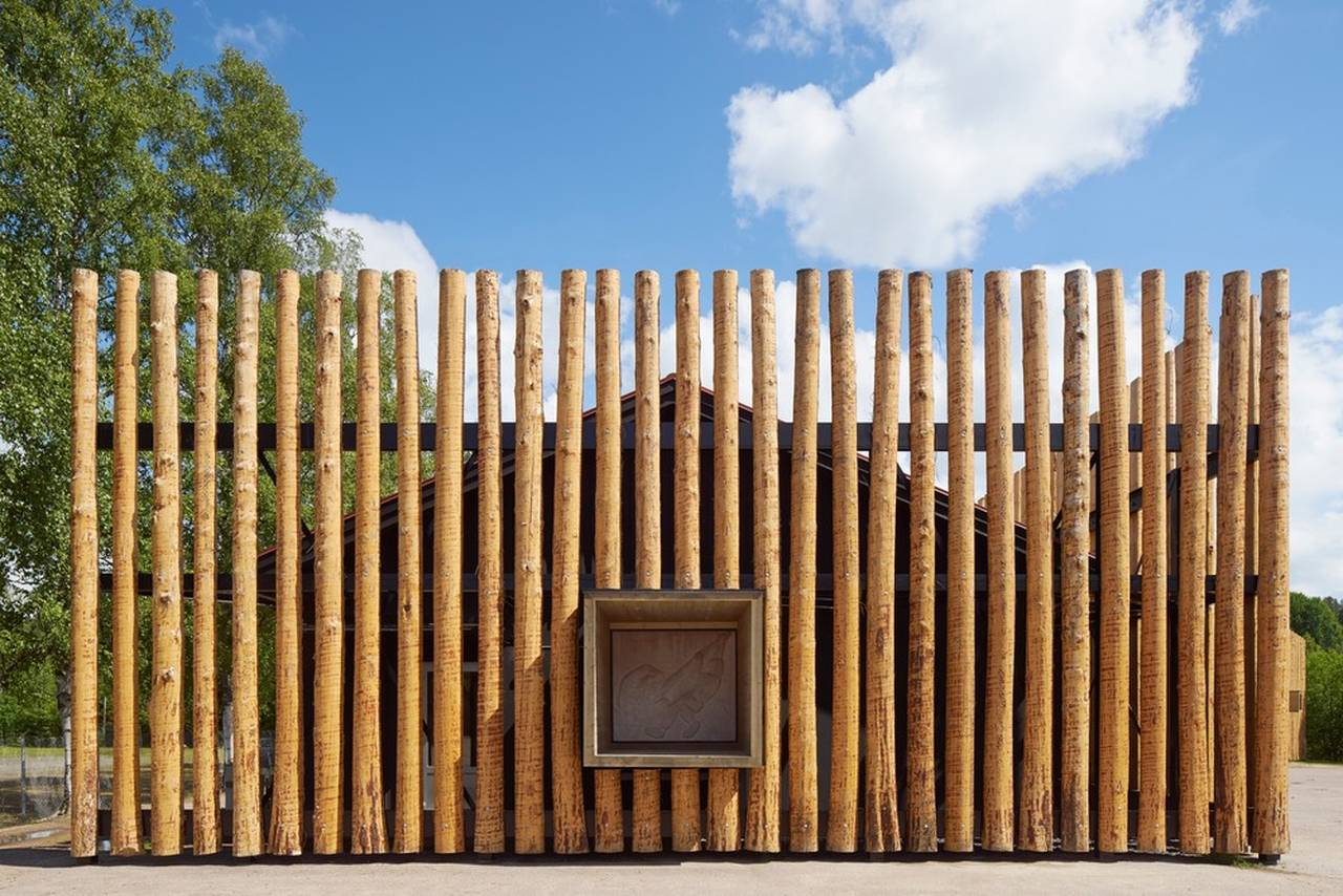 Logs cover the old school that has been painted black to appear only as a shadow behind the screen of timber : Photo credit © Åke E:son Lindman