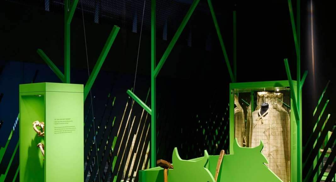 Stylized trees from green steel hold the exhibition, the green colour of the tree trunks are taken from small birch shot that just shoots up out of the earth. The floor is a printed carpet depicting the burned ground : Photo credit © Åke E:son Lindman