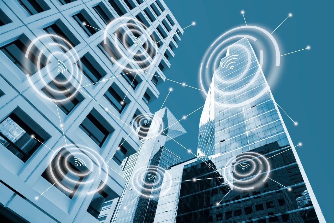 Ícono de alarma digital y vista de edificios modernos de oficinas en tono azul con un concepto de conexión de red, ciudades inteligentes y redes inalámbricas de comunicación, imágen conceptual IOT internet of things vía Shutterstock
