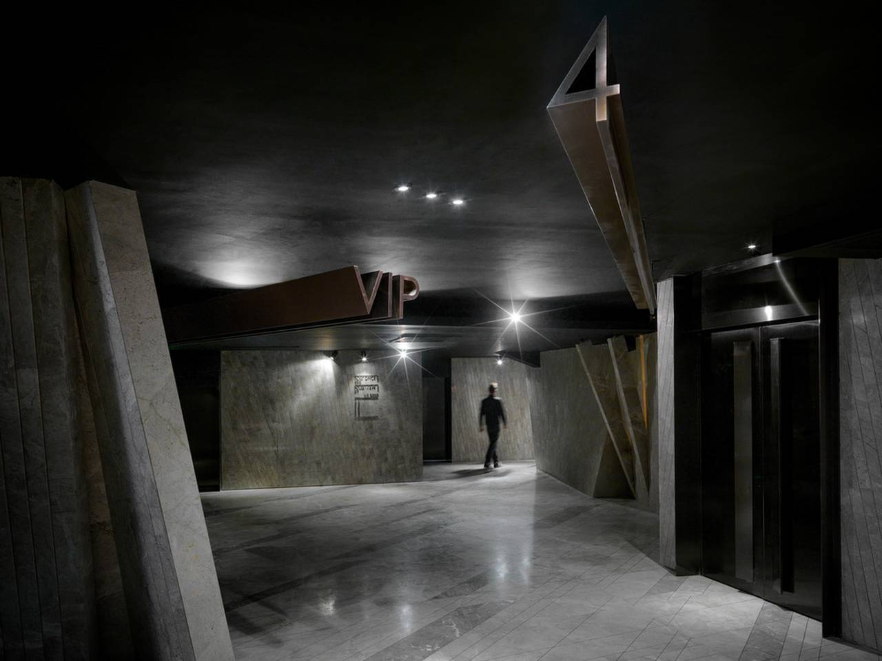 Walking through the corridor to reach the theatre, you'll find yourself walking in another form of meteor shower, which is transformed to flat rectangular shapes made out of stone, looking as if they are growing from the ground : Photo credit © One Plus Partnership Limited & Jonathan Leijonhufvud