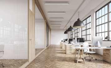 Vista frontal del interior de una oficina con una fila de mesas de madera bajo grandes ventanales. Lámparas masivas en el plafón. Computadoras, 3d rendering vía Shutterstock