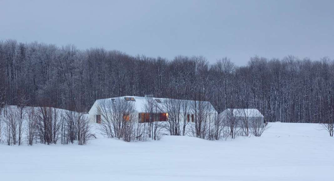 Set back into the 200-acre property and away from the road, the house is nestled into the land and against a line of trees that act as a windbreak and provide a sense of enclosure. The house virtually disappears into the snowy whiteness of the winter landscape : Photo credit © Ben Rahn / A-Frame Studio