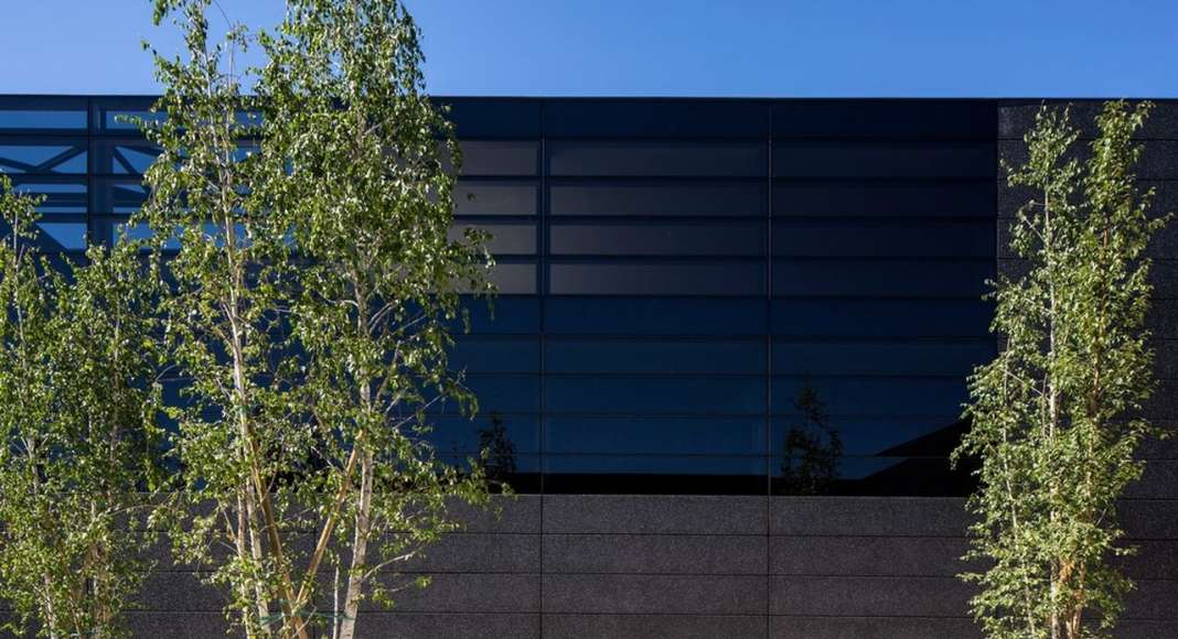 The building is covered in a ventilated skin made of black concrete and black glass : Photo credit © Massimo Crivellari