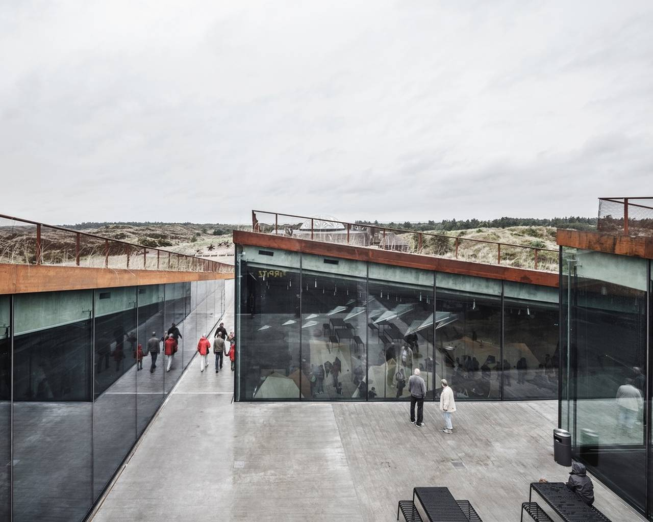 The central courtyard allows access into the four underground gallery spaces that have an abundance of daylight even though they are literally carved into the sand : Photo credit © Rasmus Hjortshoj